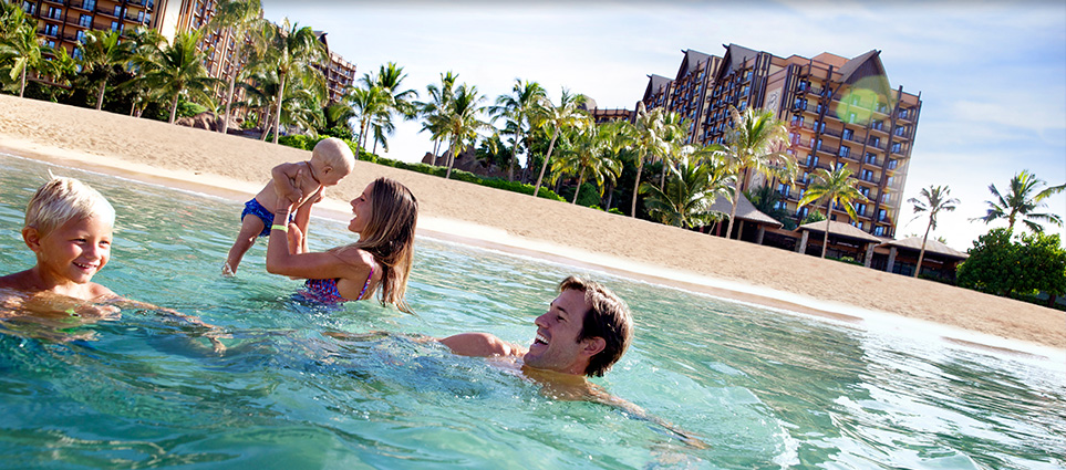 family swimming in front of Aulani Disney Resort and Spa in Oahu Hawaii